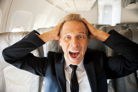 Fear of flight. Shocked mature businessman touching his head with hands and looking at camera while sitting at his seat in airplane