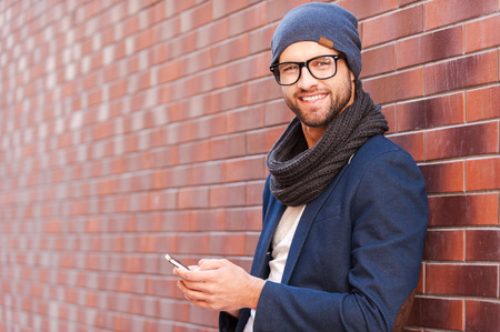Foto de Typing text message. Side view of handsome young man in smart casual wear holding mobile phone while leaning at the brick wall - Imagen libre de derechos
