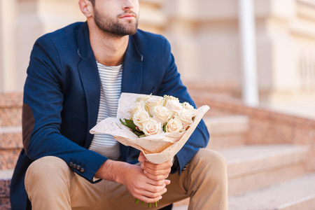 Waiting for his girlfriend. Close-up of handsome young man in smart jacket holding bouquet of flowers and while sitting on the staircase near the house