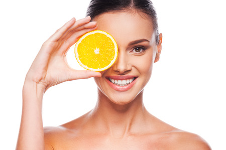 Great food for a healthy lifestyle. Beautiful young shirtless woman holding piece of orange in front of her eye while standing against white