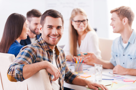 Happy to be a part of creative team. Group of cheerful business people in smart casual wear sitting together at the table and discussing something while handsome man looking at camera and smiling