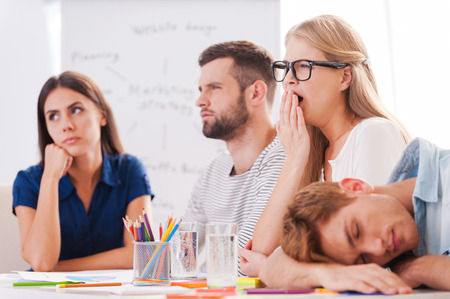 Photo pour Boring presentation. Group of young business people in smart casual wear looking bored while sitting together at the table and looking away - image libre de droit