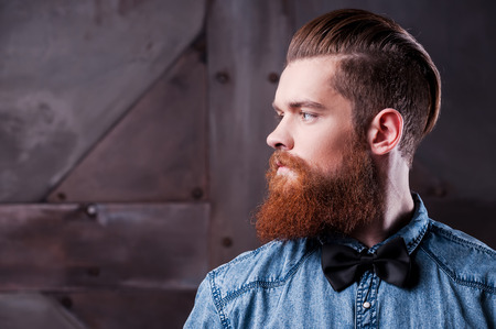 Perfect hairstyle. Profile portrait of handsome young bearded man looking away