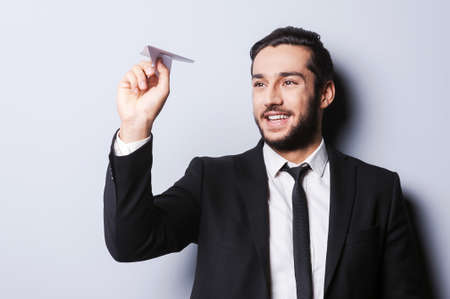Businessman with paper airplane. Playful young man in formal wear holding paper airplane and smiling while standing against grey