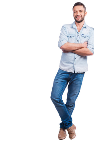 Photo pour Casually handsome. Full length of handsome young man in casual wear leaning at copy space and smiling while standing against white background - image libre de droit