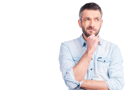Photo pour Feeling uncertain about?Frustrated young man in casual wear holding hand on chin and looking away while standing isolated on white background - image libre de droit