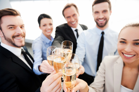 Toasting to success. Group of business people toasting with champagne and smiling while standing close to eachの写真素材