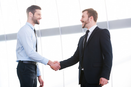 Photo pour Sealing a deal. Two cheerful business men shaking hands and smiling while standing indoors - image libre de droit