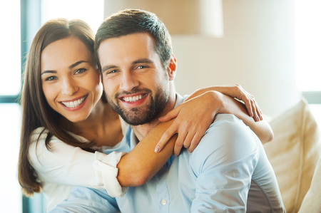 Photo pour Enjoying every minute together. Beautiful young loving couple sitting together on the couch while woman embracing her boyfriend and smiling - image libre de droit