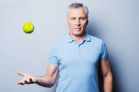 Confident senior man in casual throwing a green apple up and smiling while standing against grey background