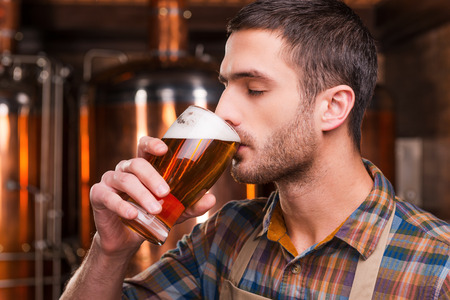 Tasting fresh brewed beer. Handsome young male brewer in apron tasting fresh beer and keeping eyes closed while standing in front of metal containers