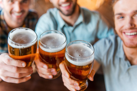 Photo pour Cheers to success! Top view of three happy young men in casual wear toasting with beer while sitting in bar together - image libre de droit