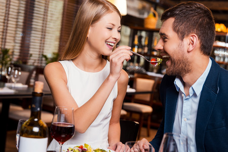 Photo pour Try my meal! Beautiful young loving couple enjoying dinner at the restaurant while woman feeding her boyfriend with salad - image libre de droit