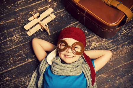 Photo pour Dreaming of a big sky. Top view of happy little boy in pilot headwear and eyeglasses lying on the hardwood floor and smiling while wooden planer and briefcase laying near him - image libre de droit