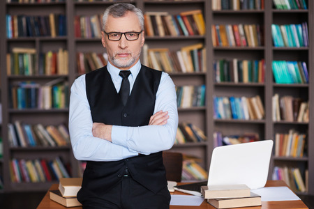 Confident professor. Confident grey hair senior man in formalwear keeping arms crossed and looking at camera while leaning at the table and with bookshelf in the background