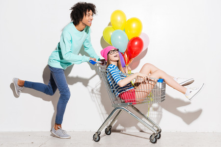 Photo pour Spending great time together. Happy young man carrying his beautiful girlfriend in shopping cart and smiling while running against grey background - image libre de droit