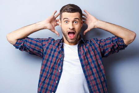 This is amazing! Surprised young man in casual shirt keeping mouth open and staring at camera while standing against grey background