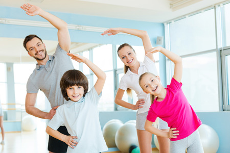 Foto de Family exercising. Happy sporty family doing stretching exercises in sports club - Imagen libre de derechos
