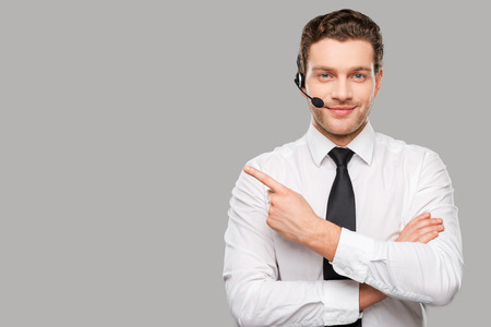 Photo pour Operator pointing copy space. Handsome young man in formalwear and headset looking at camera and pointing away while standing against grey background - image libre de droit