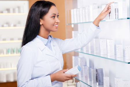 Choosing the right medicine for you. Beautiful young African woman in lab coat choosing medicine while standing near the self in drugstore