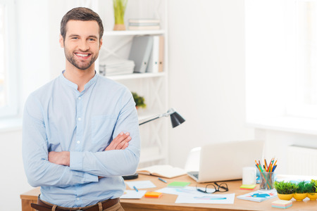 Foto de He got creative mind. Handsome young man in shirt keeping arms crossed and smiling at camera while leaning at the desk in office - Imagen libre de derechos
