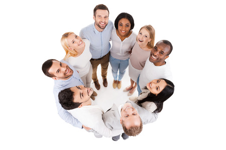 Happy united team. Top view of positive diverse group of happy people in smart casual wear bonding to each other and standing in circle