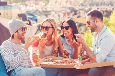 Pizza time. Four young happy people eating pizza and drinking beer while sitting at the bean bags on the roof of the building