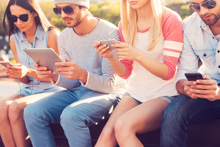 Photo for Youth culture. Four young people sitting close to each other and looking at their gadgets - Royalty Free Image