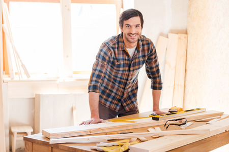 Smiling woodworker. Cheerful young male carpenter leaning at the wooden table with diverse working tools laying on it