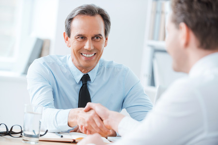 Photo for Sealing a deal. Two business people shaking hands while sitting at the working place - Royalty Free Image
