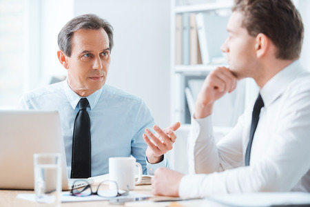 Foto de Wise advice for business nice. Two business people in formalwear discussing something while sitting at working place - Imagen libre de derechos