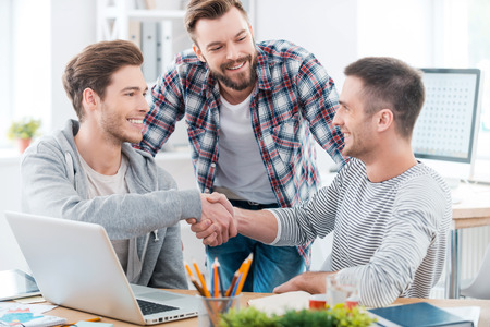 Good job! Two cheerful young men sitting at the desk and shaking hands while another man standing near and smiling