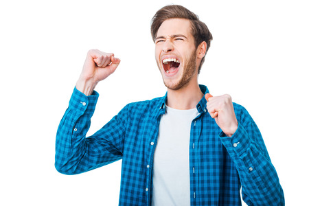 Photo pour The win is in my pocket. Excited young man keeping arms raised and expressing positivity while standing against white background - image libre de droit