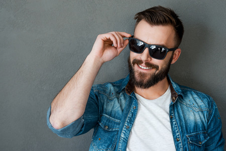 Rugged and manly. Smiling young man adjusting eyewear and looking away while standing against grey background