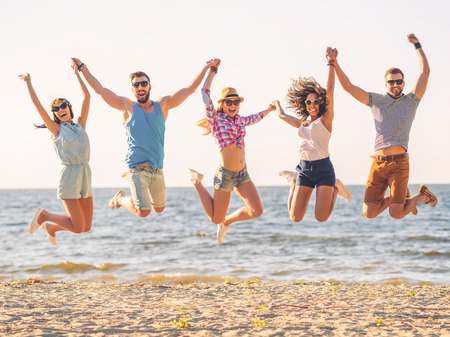 Photo pour Summer fun. Group of happy young people holding hands and jumping with sea in the background - image libre de droit