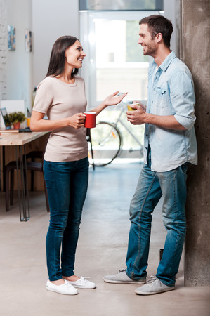 Photo pour Coffee break. Full length of two cheerful young people talking and smiling during a coffee break in office - image libre de droit