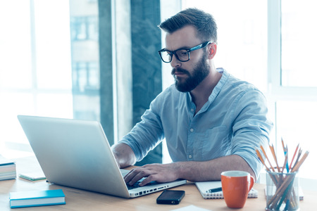 Photo for Concentrated on work. Concentrated young beard man working on laptop while sitting at his working place in office - Royalty Free Image