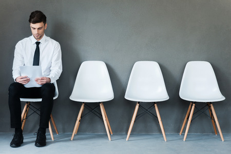 Photo pour Waiting for interview. Confident young businessman holding paper while sitting on chair against grey background - image libre de droit