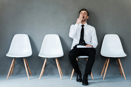 Tired of waiting. Tired young businessman holding paper and yawning while sitting on chair against grey background