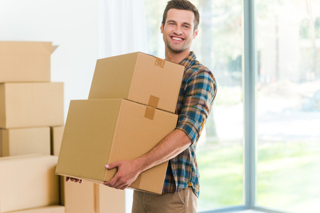 Photo pour Moving to a new apartment. Cheerful young man holding a cardboard boxes and smiling at camera while other carton boxes laying on background - image libre de droit