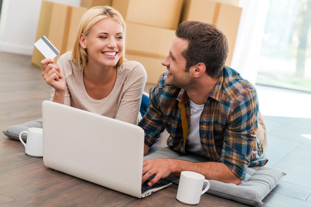 Photo pour Online shopping makes life easier. Smiling young couple laying on the floor of their new apartment and shopping through Internet while cardboard boxes laying in the background - image libre de droit