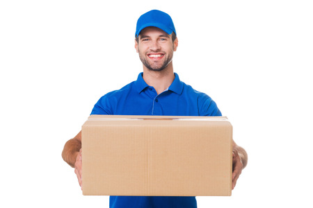 Take your package! Happy young courier stretching out a cardboard boxand smiling while standing against white background