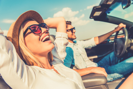 Photo pour Freedom of the open road. Side view of joyful young woman relaxing on the front seat while her boyfriend sitting near and driving their convertible - image libre de droit