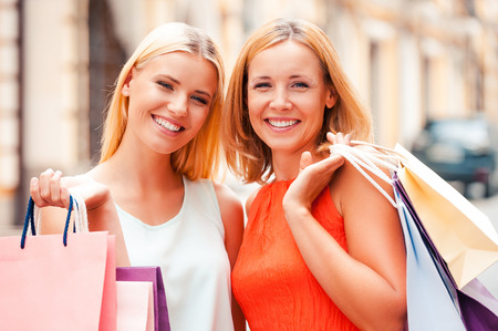 Foto de Mother and daughter are the best friends. Beautiful mature woman and her blond hair daughter holding shopping bags and looking at camera while standing outdoors - Imagen libre de derechos