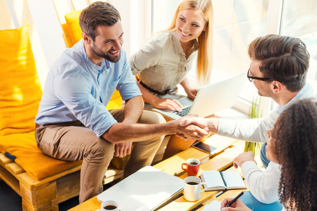 Foto de Congratulations! Two cheerful young men sitting at the wooden desk in office and shaking hands while two beautiful women looking at them and smiling - Imagen libre de derechos
