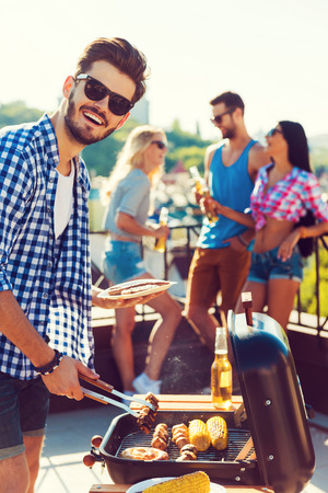 Tasty food and good company. Happy young man barbecuing and looking at camera while three people having fun in the background