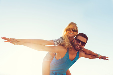 Photo pour High flying romance. Low angle view of smiling young man piggybacking his girlfriend while keeping arms outstretched - image libre de droit
