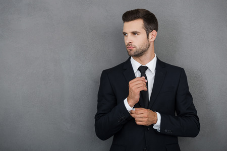 Photo pour Perfect to the last detail. Handsome young businessman adjusting his sleeves while standing against grey background - image libre de droit
