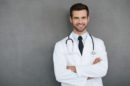You can absolutely trust me. Confident young doctor in white uniform looking at camera and keeping arms crossed while standing against grey background