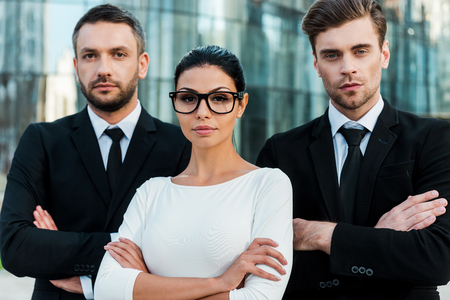 Faces of new business. Three confident business people keeping arms crossed and looking at camera while standing outdoors